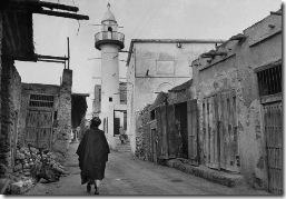 عالم دين شيعي يتمشى في أزقة المحرق