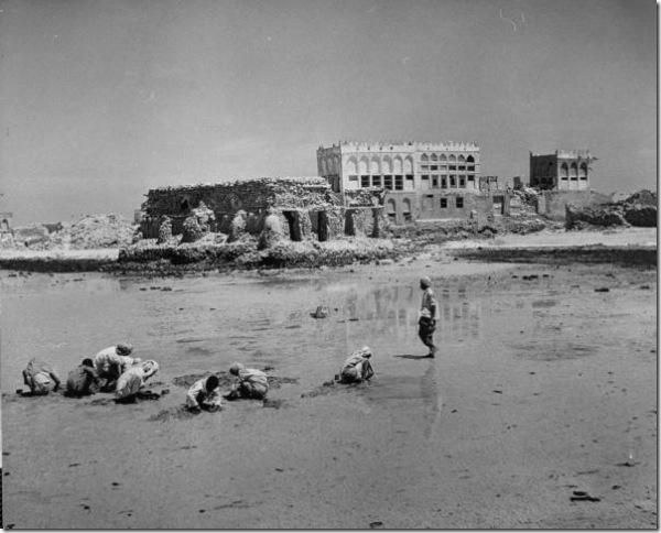 أطفال يحفرون على الشاطئ بحثاً عن المحار