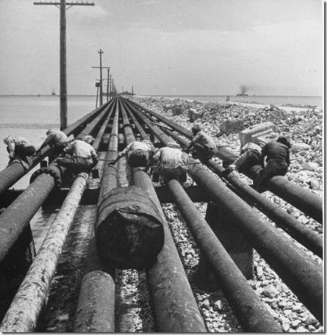 عمال يعملون في انابيب نفط موصولة من محطة التكرير الى ميناء التصدير